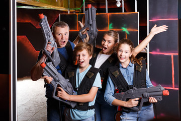 Cheery teens and parents with laser guns