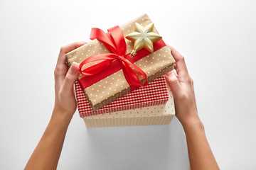 Woman hands holding Christmas gifts on a white background viewed from above. Top view. Personal perspective
