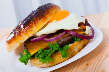Delicious hamburger with beef cutlet, fried egg, lettuce and cheese