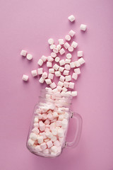 View from above of white and pink marshmallows in glass on pink background