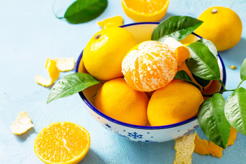 Fresh and juicy tangerines in a bowl on blue a stone or slate background. Seasonal, food background. Copy space.