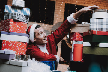 Young Man in Santa Claus Costume with Gift Boxes.