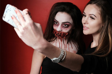 Concept selfie makeup for the story in the style of Halloween. A beautiful girl together with another girl in the image of a witch are taking pictures of themselves on the phone. Red background.