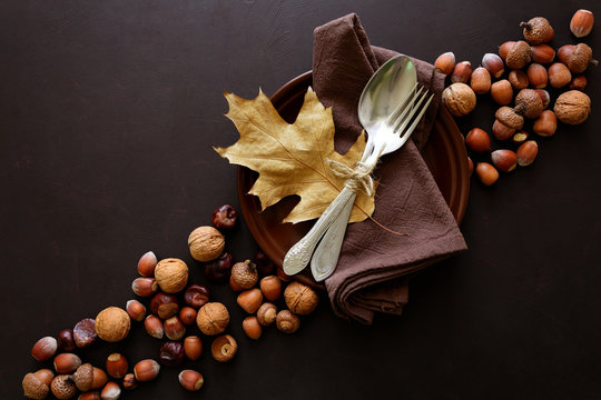 Tableware, walnuts, hazelnuts, chestnuts and acorns on dark wooden background. Thanksgiving day holiday concept. Top view. Flat lay. Copy space