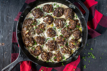 Meatballs in cream sauce in cast iron pan top view