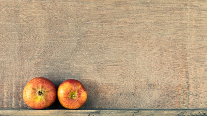 wooden background with two small apples