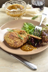 Fried pork chop with fresh herbs and fruit sauce, vertical