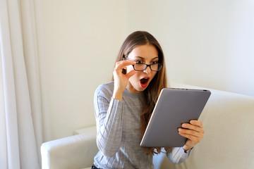 Closeup portrait, upset young woman, astonished surprised, wide open mouth, large eyes in black glasses by what she sees on her gray silver tablet pad on sofa at home