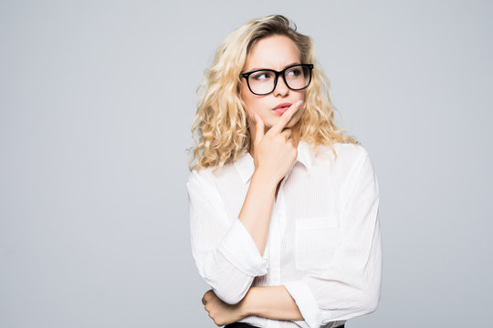 Beautiful thinking blonde business woman isolated white background