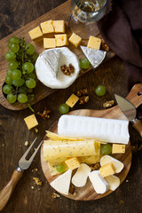 Cheese plate. Assortment of cheeses, grapes and nuts on dark rustic wooden table. Top view flat lay background.