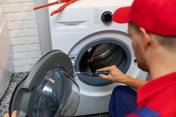 repairman with screwdriver repairing washing machine door