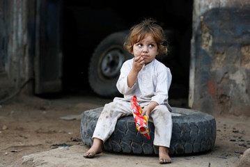 Four-year-old Ramesha, eats from her pack of locally made food, as she sits on a tyre at a workshop in a neighbourhood in Karachi