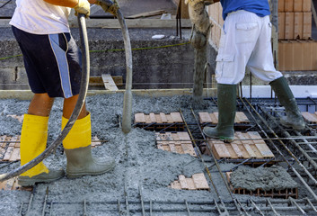 Construction workers pour concrete for the execution of a reinforced concrete floor. The concrete is vibrated after casting