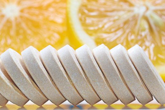 Row of  Vitamin c tablets and fresh lemon