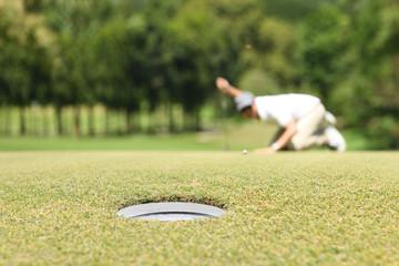 Man golfer check line for putting golf ball on green grass