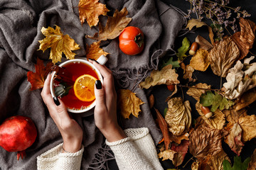 Autumn composition. A cup of fragrant tea with lemon on a dark table with autumn leaves and flowers.