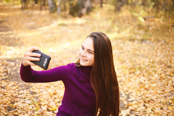 Cute girl with a smartphone in the autumn forest.