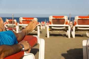 Man tanning with all inclusive bracelet on orange hammock on the beach. Resort, wristband, summer...