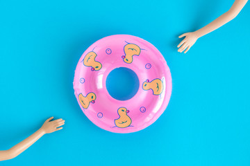 Doll hands trying to reach inflatable pool float toy against blue background.