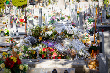 Flowers, candles, lights on the graves and tombs in the autumn sun. Colorful polish cemetery. Before All Saints' Day. Gniezno, Poland.