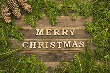 Inscription Merry Christmas on a wooden background. Frame made of fir branches and cones. Holiday concept