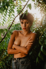 Alluring topless woman in green leaves