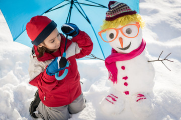 Child with snowman on snow with umbrella