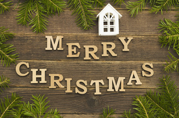 Inscription Merry Christmas on a wooden background. Frame of fir branches, a small house.
