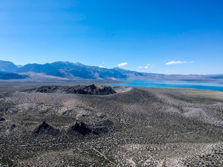 drone view of a lake in the desert with mountains background.