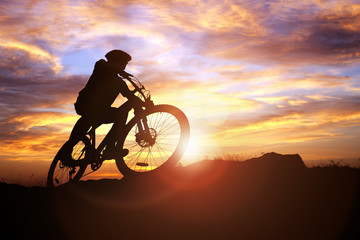 Mountain biker silhouette in action against the sunset concept for sport and exercise
