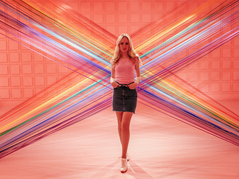 Young beautiful blonde girl on a pink background of colorful threads