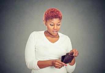 Sad poor woman showing her empty wallet