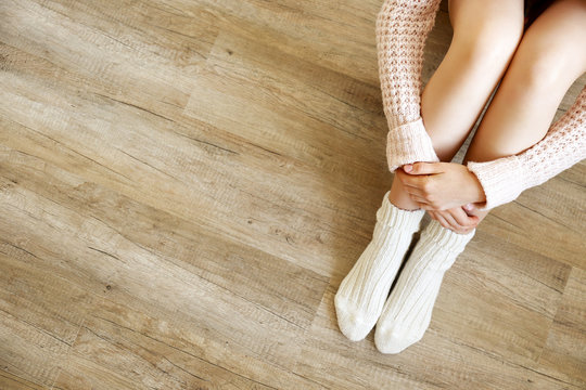 Lonely woman concept. Young female wearing woolen socks, knitted sweater, sitting alone in empty room with wood textured laminated floor. Background, copy space, top view, close up.