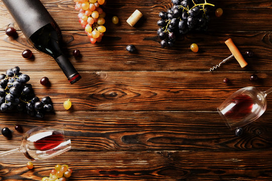 Vintage bottle of red wine with blank matte black label, poured glass, corkscrew & grapes, grunged wood table background. Expensive bottle of cabernet sauvignon concept. Copy space, top view, flat lay
