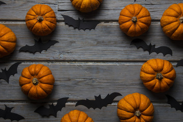 Halloween pumpkins and black vampire bats on a wooden background