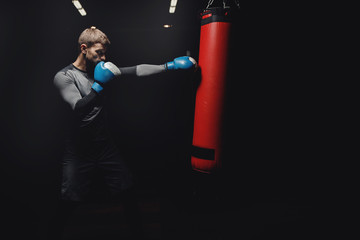 Young male boxer hitting punching bag on black background in gym.