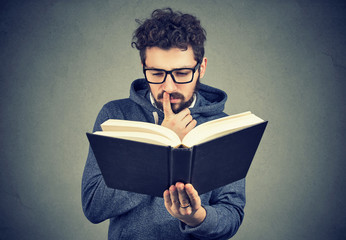 Puzzled man reading a book