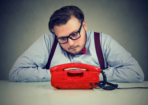 Desperate sad man waiting for someone to call him