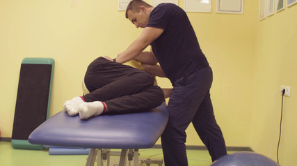 Doctor physiotherapist helping young disabled man, doing leg exercises at the rehabilitation center. Health reductive gymnastics.
