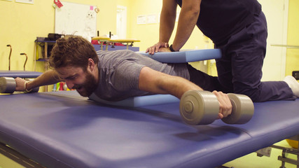 Young disabled man doing exercises with dumbbells at the rehabilitation center. Doctor physiotherapist helping him. Healthy gymnastics. Active people.