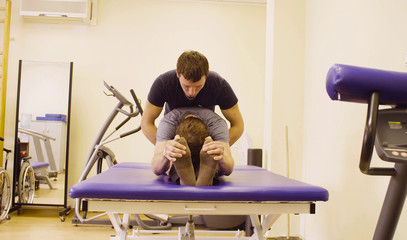 Doctor physiotherapist doing recovery exercises for young disable man at the rehabilitation clinic