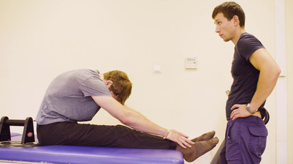 Doctor physiotherapist helping young disable man to do the recovery exercise at the rehabilitation clinic