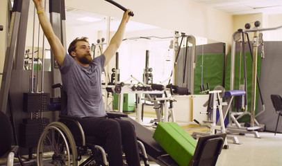 Young disabled man in wheelchair doing strength exercises for hands at the rehabilitation clinic