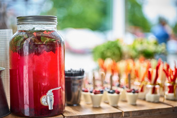 Tasty appetizers served in glass jars on wooden table.
