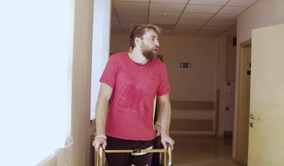 Portrait of young disabled man walking holding a walking frame through the corridor of the rehabilitation clinic. Expression of an effort