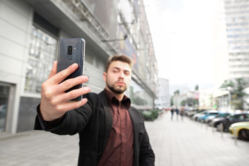 Business man with beard standing against the background of the city and take selfie on smartphone. Focus on the smartphone. Selfies concept.