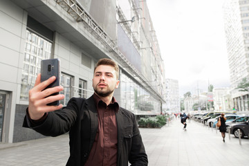 Portrait of a business man with a beard and dressed in a suit, walking around the streets of the city and takes selfie. Man speaks on video communication on the street.