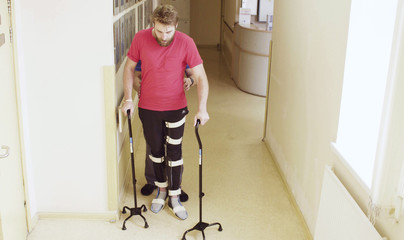 Young disable man in orthosis walking with support of two walking cane in the rehabilitation clinic. Doctor helping him.