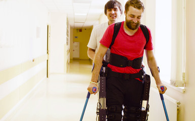 Young disable man in the robotic exoskeleton sitting in wheelchair in the rehabilitation clinic