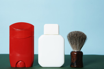 Shaving brush, lotion and deodorant for men on table against color background